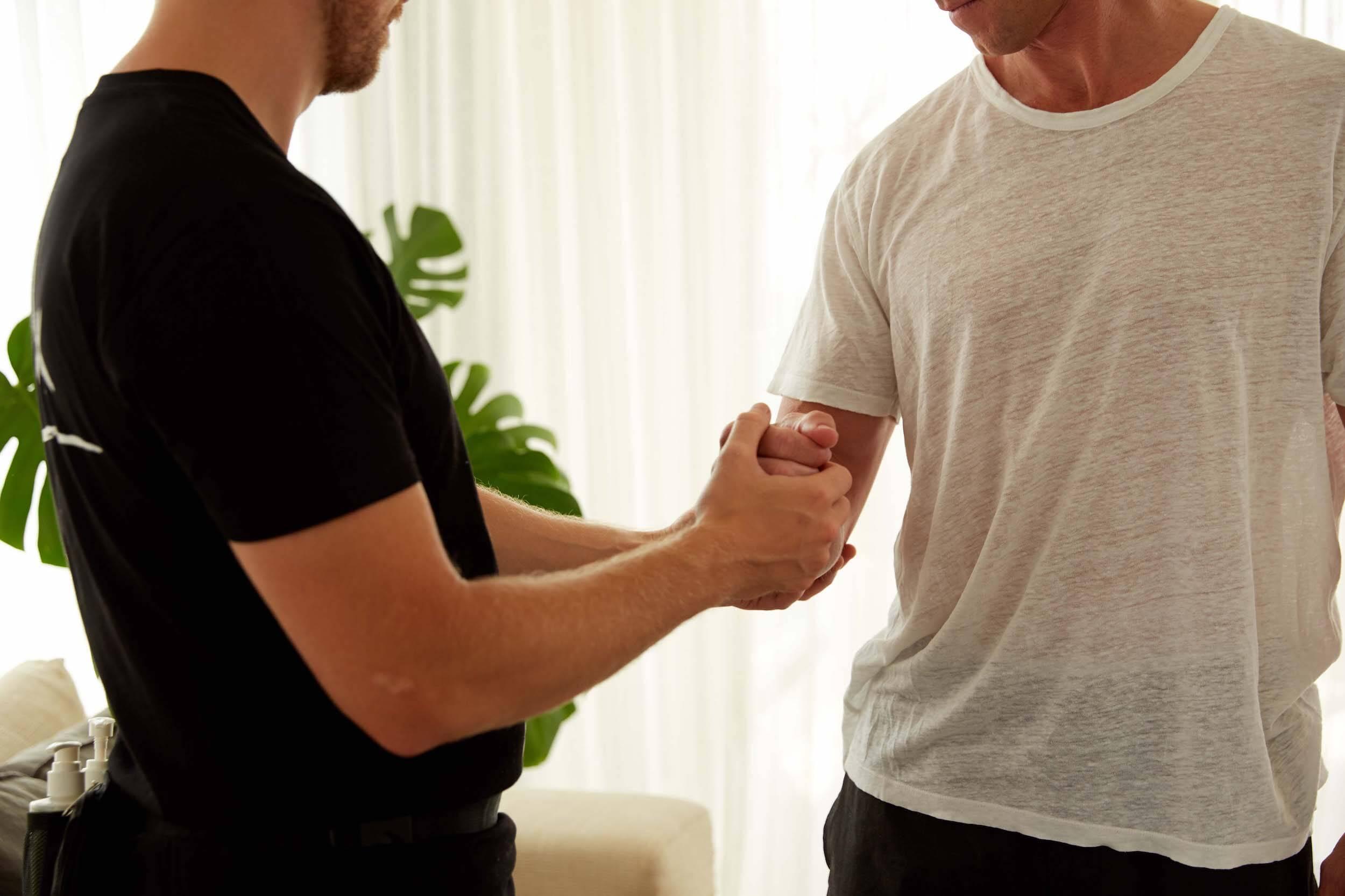 Physio examining client's arm